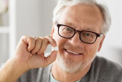 medicine, healthcare and people concept - portrait of happy smiling senior man holding white round pill