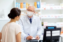 medicine, healthcare and people concept - senior apothecary wearing face protective medical mask for protection from virus disease writing prescription for female customer at pharmacy
