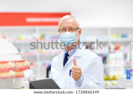 medicine, healthcare and technology concept - senior apothecary wearing face protective medical mask for protection from virus disease with tablet pc computer at pharmacy