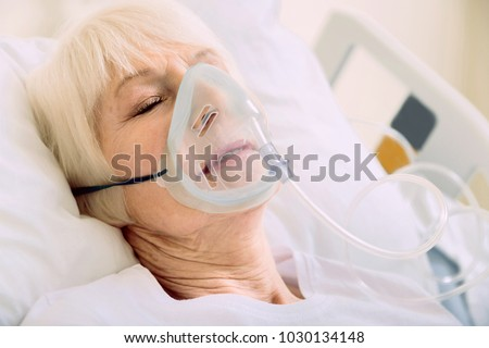 Medicine is the best medicine. Ill senior woman lying in a hospital bed while wearing an oxygen mask and undergoing treatment. #1030134148