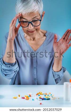 Medicine non-adherence. Confused senior woman looking at her medicines on the table.  Stock photo ©
