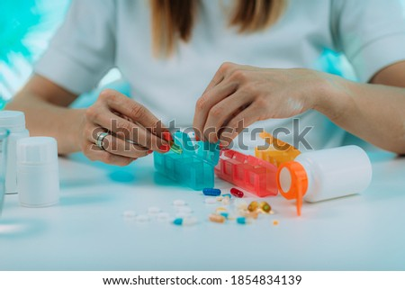 Medicine non adherence. Woman holding pills in her hand, not sure if she had taken the medicine or not  Stock photo ©
