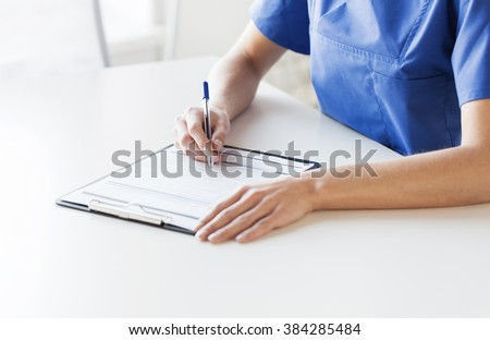 medicine, people and healthcare concept - close up of female doctor or nurse writing medical report to clipboard at hospital