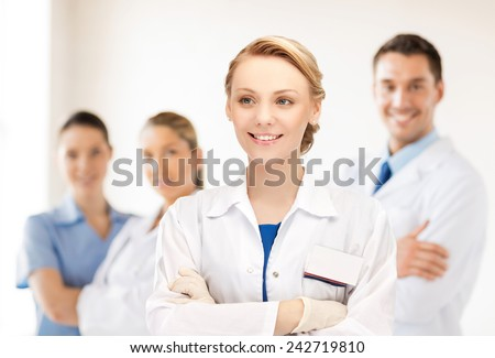 medicine, people, profession and teamwork concept - smiling young female doctor in white coat over group of medics in hospital