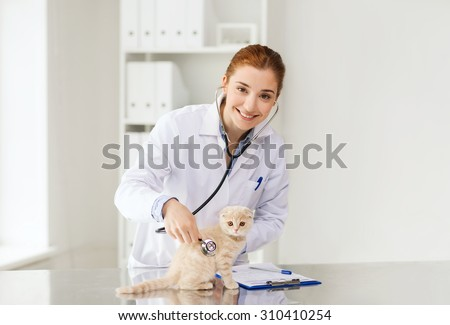 medicine, pet, animals, health care and people concept - happy veterinarian doctor with stethoscope checking scottish fold kitten up at vet clinic