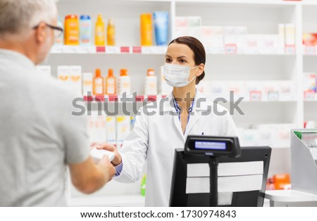 medicine, pharmaceutics and healthcare concept - apothecary wearing face protective medical mask for protection from virus disease and senior man customer buying drug at pharmacy
