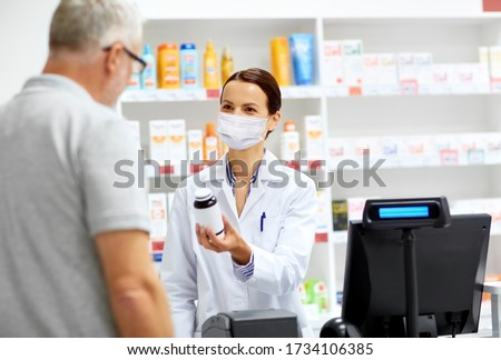 medicine, pharmaceutics and healthcare concept - apothecary wearing face protective medical mask for protection from virus disease and senior male customer buying drug at drugstore