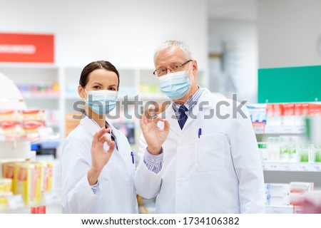 medicine, pharmaceutics and healthcare concept - happy smiling apothecaries wearing face protective medical masks for protection from virus disease at pharmacy showing ok hand sign ストックフォト ©