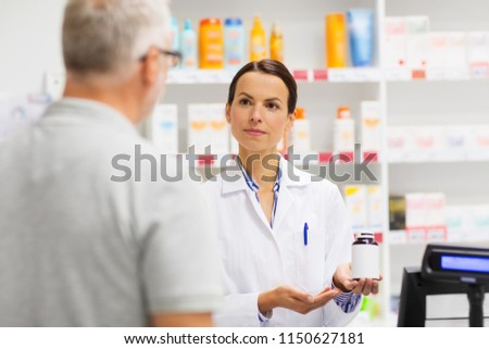 medicine, pharmaceutics, health care and people concept - apothecary showing drug to senior man customer at drugstore