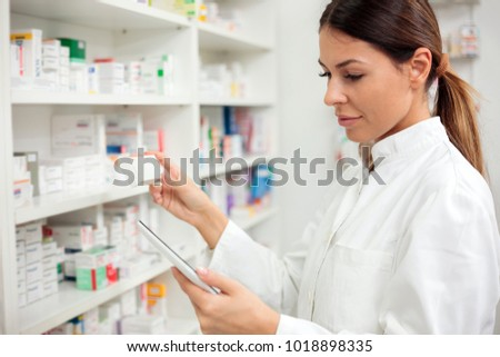 Medicine, pharmaceutics, health care and people concept - Serious young female pharmacist taking medications from the shelf. #1018898335