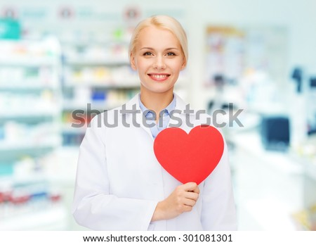 medicine, pharmacy, people, health care and pharmacology concept - happy young woman pharmacist holding red heart shape over drugstore background
