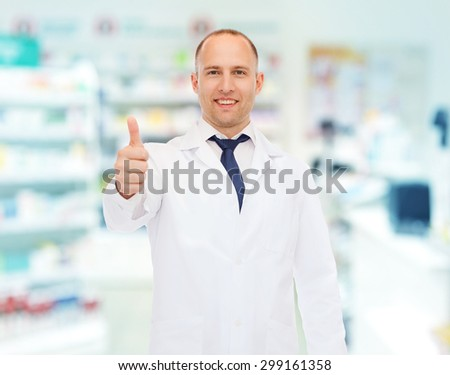 medicine, pharmacy, people, health care and pharmacology concept - smiling male pharmacist in white coat showing thumbs up over drugstore background