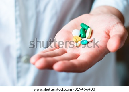 Medicine pills or capsules in hand, palm or fingers. Drug prescription for treatment medication. Pharmaceutical medicament, cure in container for health. Antibiotic, painkiller closeup.