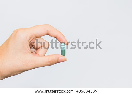 Medicine pills or capsules in hand, palm or fingers. Drug prescription for treatment medication. Pharmaceutical medication, cure in container for health. Antibiotic, painkiller close up. #405634339