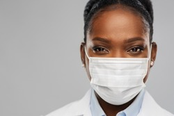 medicine, profession and healthcare concept - close up of african american female doctor or scientist in protective facial mask over grey background