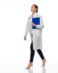 medicine, profession and healthcare concept - happy smiling female doctor in white coat with stethoscope and clipboard walking with clipboard