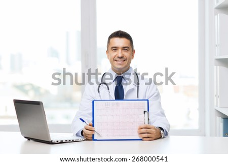 medicine, profession, technology and people concept - happy male doctor with clipboard and laptop computer in medical office