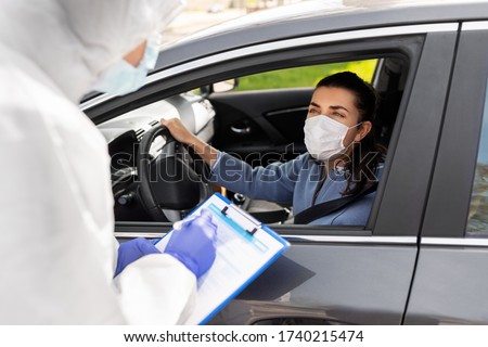 medicine, quarantine and pandemic concept - doctor or healthcare worker in protective gear, medical mask, gloves and goggles with clipboard and woman waiting for coronavirus test in her car