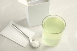Medicine sachet, spoon and glass with dissolved drug on table indoors