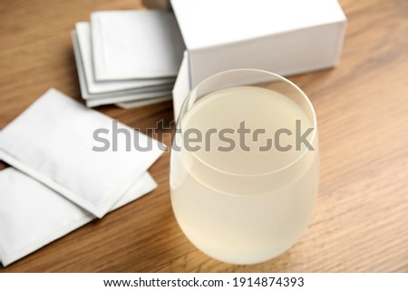 Medicine sachets and glass of water on wooden table Foto d'archivio ©