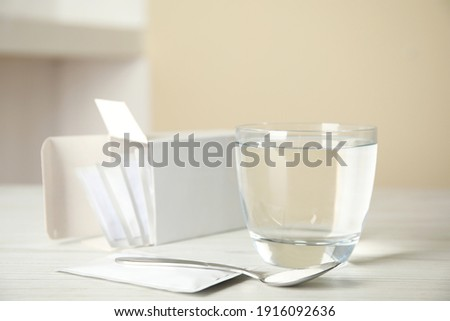 Medicine sachets, glass of water and spoon on white table Foto d'archivio ©