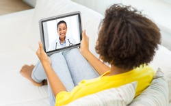 medicine, technology and healthcare concept - african young female patient having video chat with doctor on tablet pc computer at home