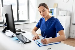 medicine, technology and healthcare concept - female doctor or nurse with clipboard working at hospital