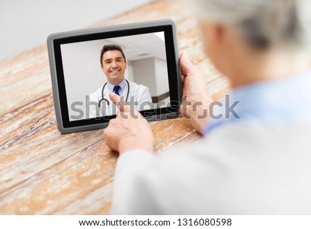 medicine, technology and healthcare concept - senior woman patient having video call with doctor on tablet pc computer at home
