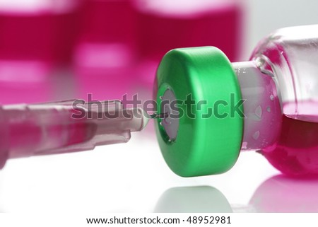Medicine vial and syringe with pink liquid