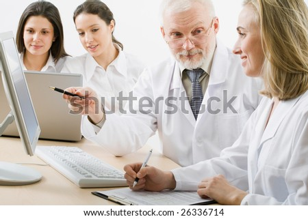 Medicine workers looking at monitor
