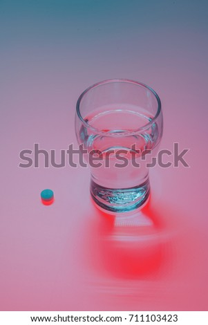 Medicines And Drinking Glass Colorful, conceptual image a glass of water with pink medication tablet #711103423