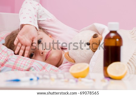 Medicines and hot tea in front, sick girl with teddy bear in bed ( No-name teddy bear )