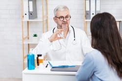 Medicines, drops for nose, eyes, ears. Serious old man doctor in white coat and glasses shows bottle to lady patient at table with jars of pills, sanitizer and laptop in office interior, empty space