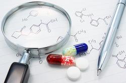 Medicines, magnifier and structure formula. Examining medicine.