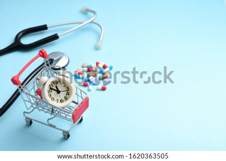 Medicines, stethoscopes and clocks in shopping carts on a blue background