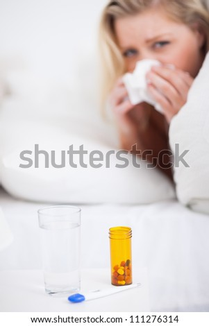 Medicines with a blonde woman sneezing in her bed in background
