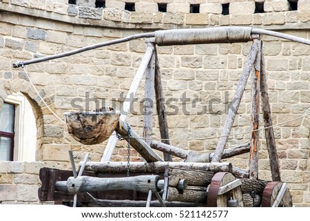 Medieval ancient weapon firing nuclei in a guarded castle. Vintage weapon catapult. Wooden medieval catapult ballistic device. Trebuchet catapult Medieval weapon in castle. Wooden ancient catapult.
