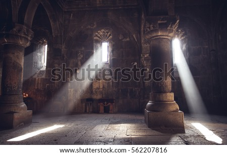 Medieval Armenian christian church interior with sun rays from the window falling on the candles. Religion, old architecture, christianity, travel, belief concept.