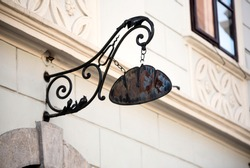 Medieval bakery sign - metal ornaments and loaf of bread hanging above the entrance to the bakery