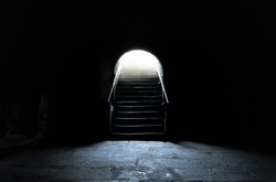 Medieval basement in complete darkness with a strong light at the exit