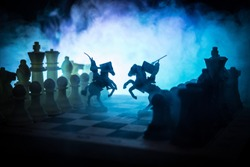 Medieval battle scene with cavalry and infantry on chessboard. Chess board game concept of business ideas and competition and strategy ideas Chess figures on a dark background with smoke and fog.