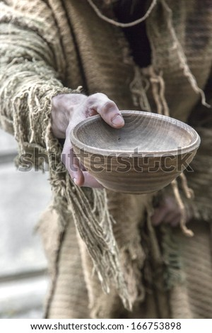 Medieval beggar holds out his wooden cup to ask for money