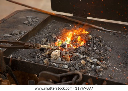 medieval blacksmith method of warming a piece of iron in the fire