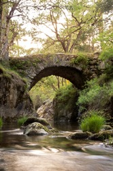 Medieval  bridge on the mountain river on sunset