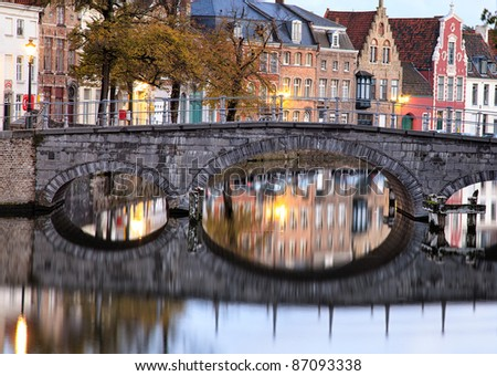 Medieval bridge over canal in Bruges, Belgium, in early morning skylight with quaint buildings reflected in the river
