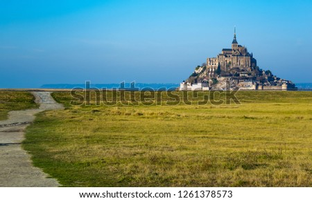 Medieval castle, against the blue sky and white clouds, the castle on the island, the castle is surrounded by water, green grass, a fortress and abbey, an incredibly beautiful castle like  fairy tale #1261378573