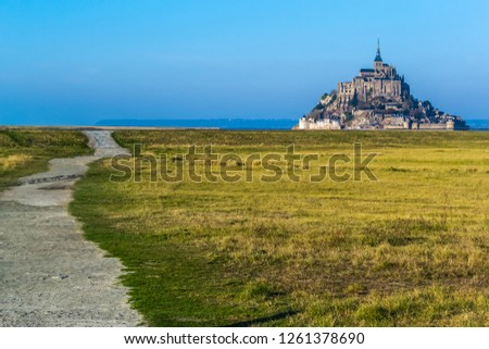 Medieval castle, against the blue sky and white clouds, the castle on the island, the castle is surrounded by water, green grass, a fortress and abbey, an incredibly beautiful castle like  fairy tale #1261378690