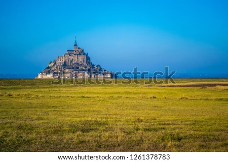 Medieval castle, against the blue sky and white clouds, the castle on the island, the castle is surrounded by water, green grass, a fortress and abbey, an incredibly beautiful castle like  fairy tale #1261378783