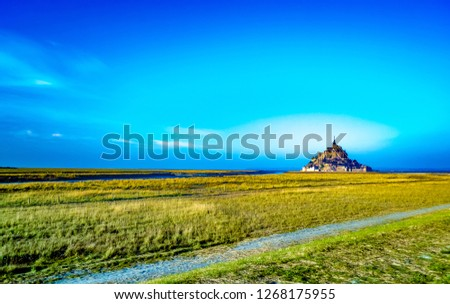 Medieval castle, against the blue sky and white clouds, the castle on the island, the castle is surrounded by water, green grass, a fortress and abbey, an incredibly beautiful castle like  fairy tale #1268175955