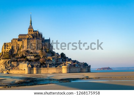 Medieval castle, against the blue sky and white clouds, the castle on the island, the castle is surrounded by water, green grass, a fortress and abbey, an incredibly beautiful castle like  fairy tale #1268175958